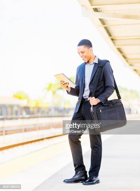 Black businessman using digital tablet on train platform