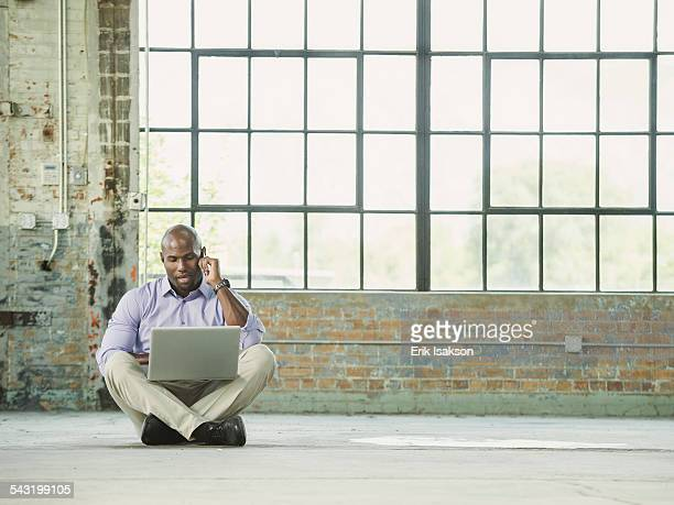 Black businessman using laptop and cell phone on warehouse floor