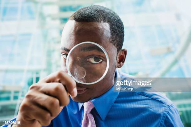 Black businessman using magnifying glass