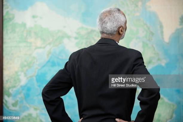 Black businessman viewing world map