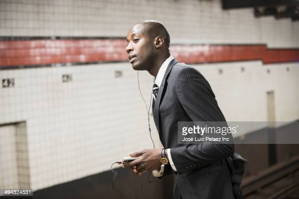 Black businessman waiting for subway on platform