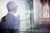 Black businessman walking by window