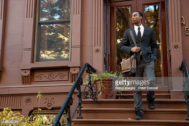 Black businessman walking down front stoop steps