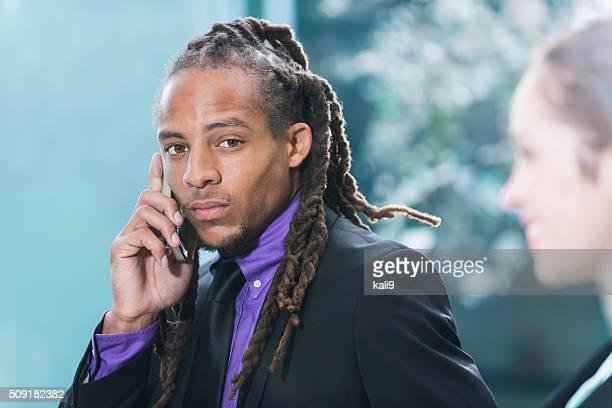 Homme d'affaires noir avec des dreadlocks à l'aide de téléphone portable
