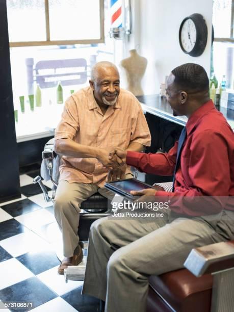 Black businessmen shaking hands in retro barbershop