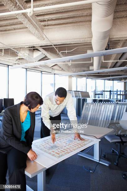 Black businesspeople looking at office floor plans