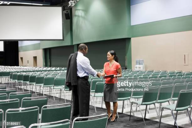 Black businesspeople shaking hands in empty conference center