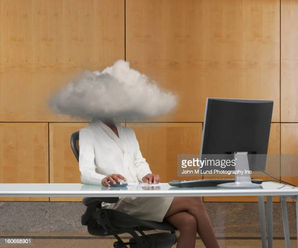 Black businesswoman at desk with head in clouds