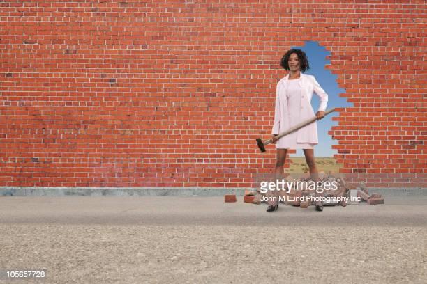 Black businesswoman breaking through brick wall