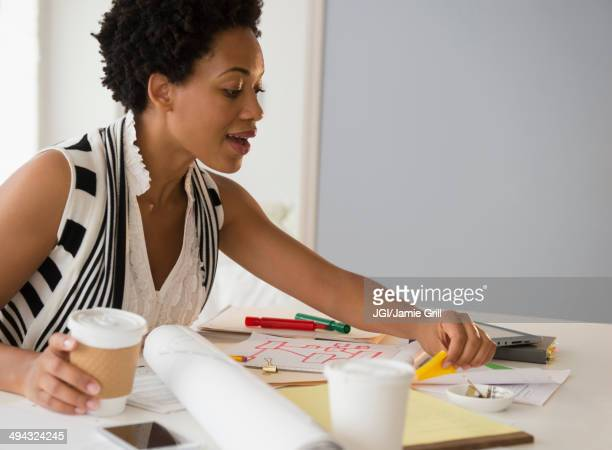 Black businesswoman drinking coffee and working