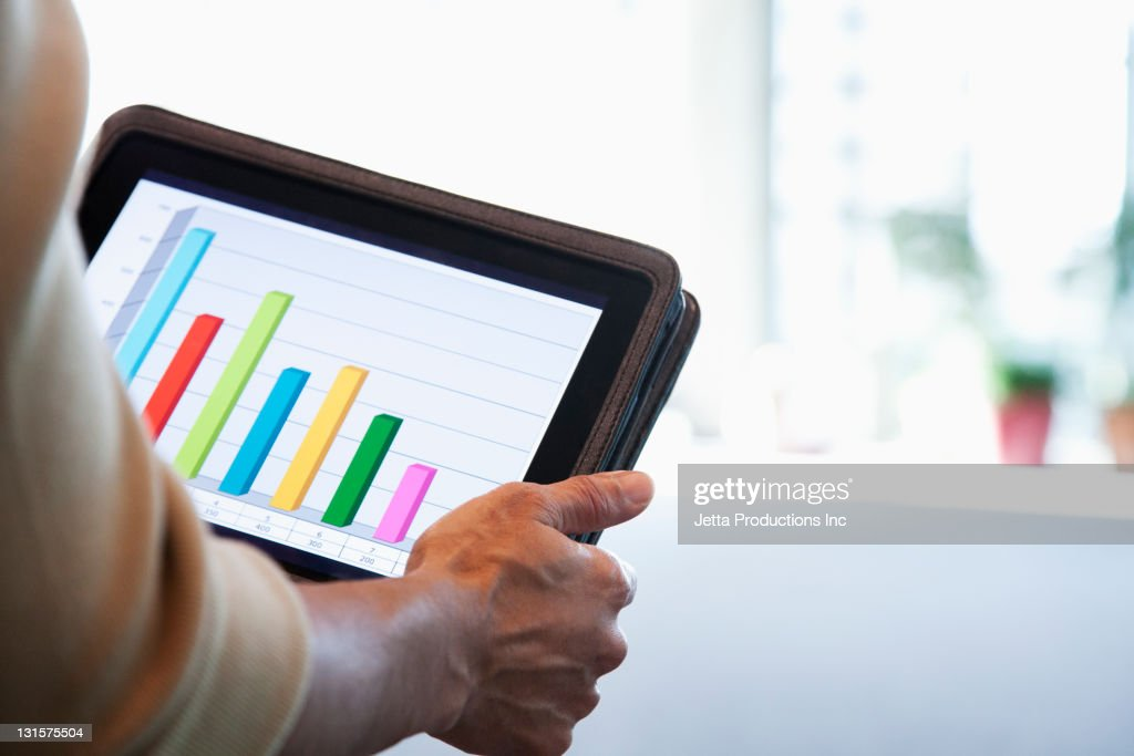 Black businesswoman looking at bar graph on digital tablet : Stock Photo