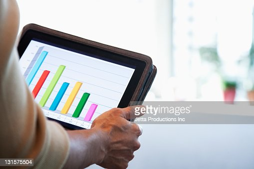 Black businesswoman looking at bar graph on digital tablet : ストックフォト