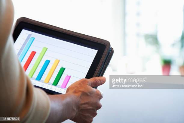 Black businesswoman looking at bar graph on digital tablet