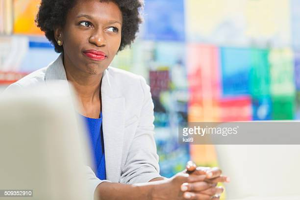 Black businesswoman sitting at table with hands clasped