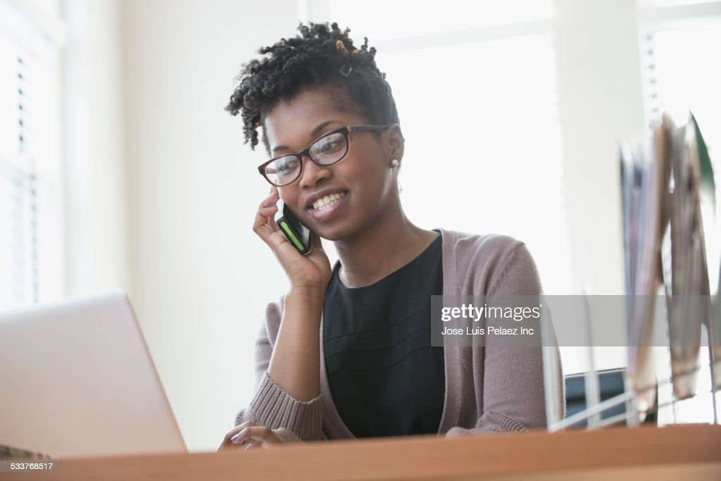 Black businesswoman talking on cell phone in office