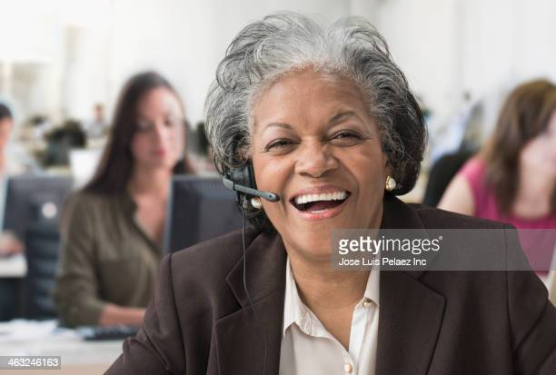 Black businesswoman talking on headset in office