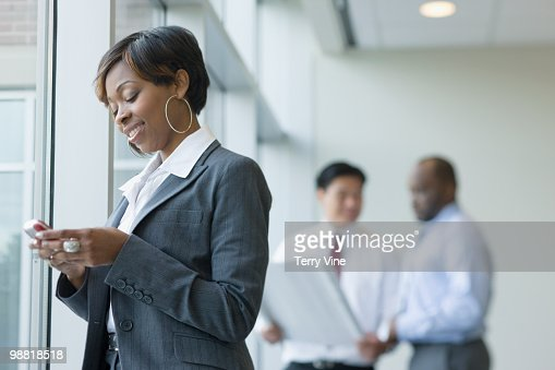 Black businesswoman text messaging on cell phone : Stock Photo