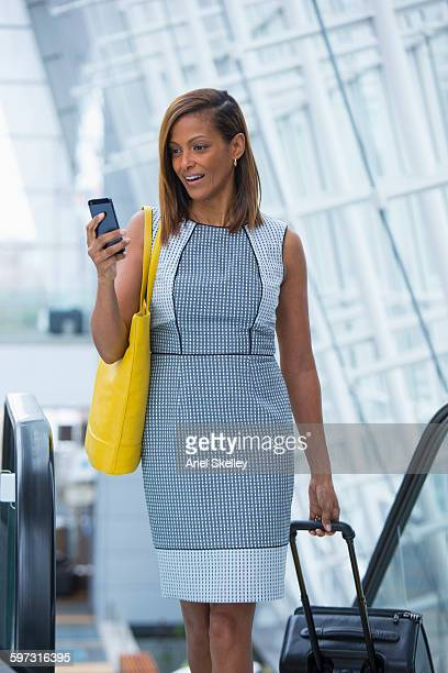 Black businesswoman using cell phone in airport
