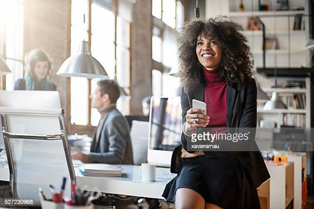 Black businesswoman using cell phone in the office