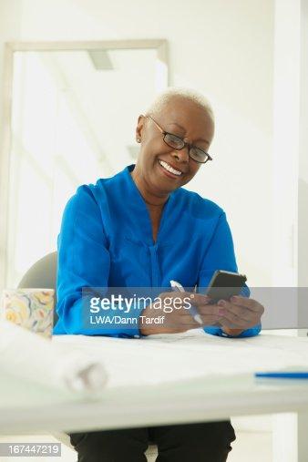 Black businesswoman using cell phone : Stock Photo