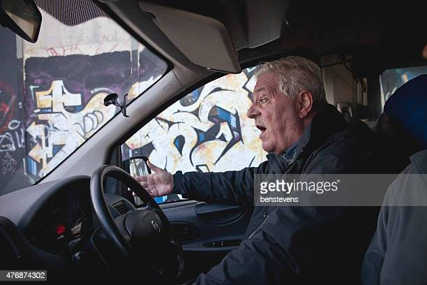 Black cab driver taking tourists through the streets of Belfast