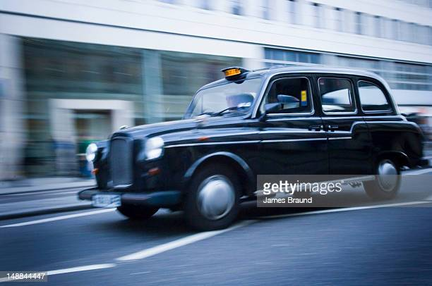 Black cab drives along the Strand.