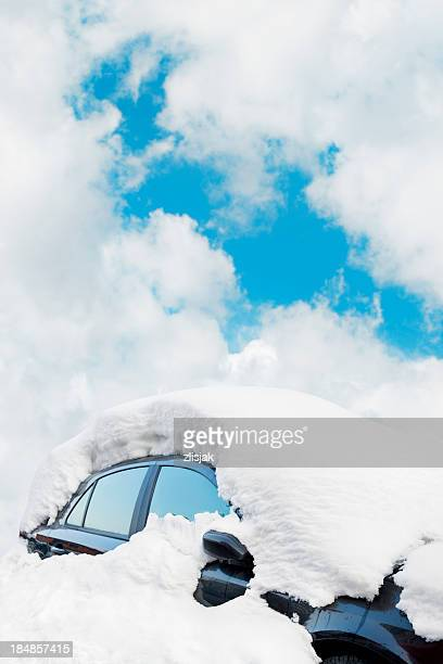 Black car covered in a thick layer of snow