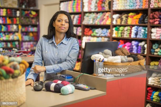 Black cashier working in yarn store