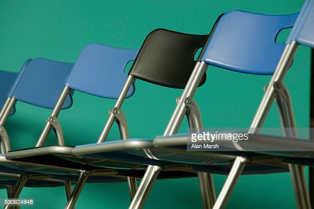 Black Chair in Row of Blue Chairs