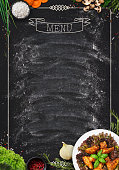 Design concept for restaurant meat and grill menu mockup. Black rustic chalkboard with white inscription and frame, top view, copy space for text and logo