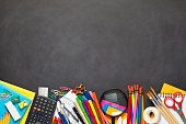Black chalkboard with school supplies coming from the bottom border of the frame. The composition includes paper clips, yellow pencils, note pad, loupe, adhesive tape, paint brushes, crayons, pencil s