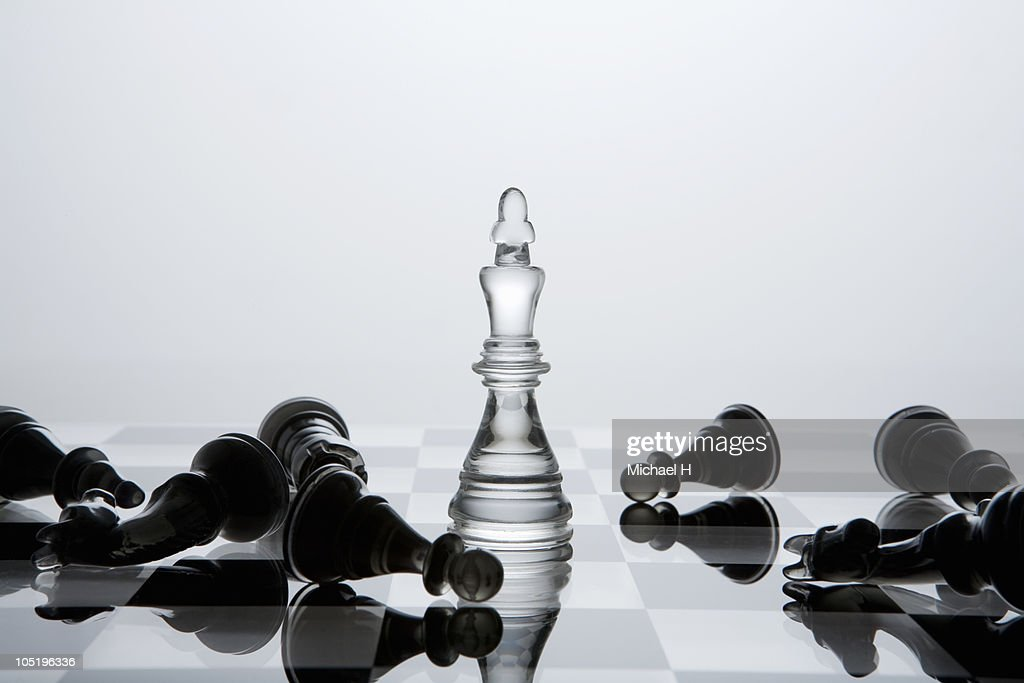 Black chessman knocked down by white king : Stock Photo