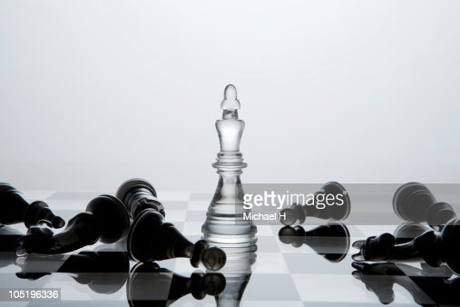 Black chessman knocked down by white king : Stock Photo