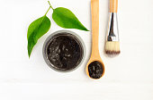 mud in jar with spoon and cosmetic brush,  white wooden background.
