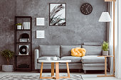 Black clock and posters on dark wall above grey settee with yellow pillow in cozy living room