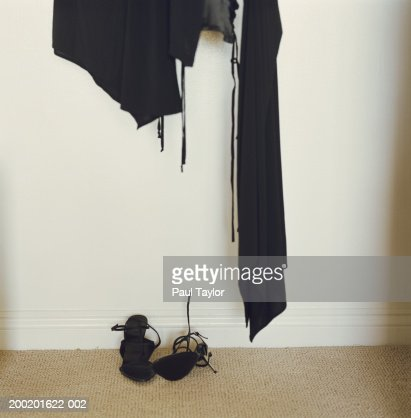 Black clothing hanging in closet, high heeled shoes on floor