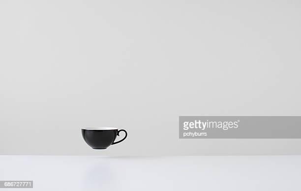 Black coffee cup floating mid air