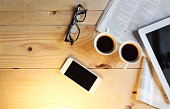 Black coffee with blank digital tablet and mobile phone, magazines and glasses on the table. Break concept