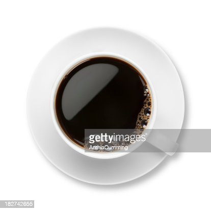 Black coffee with bubbles in white cup with saucer