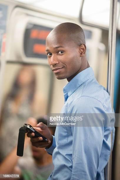 Black Pendler in U-Bahn von SMS auf Handy