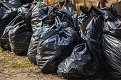 Black, complete and tied garbage bags standing together on the street,  outdoors. removal, sorting and recycling rubbish.