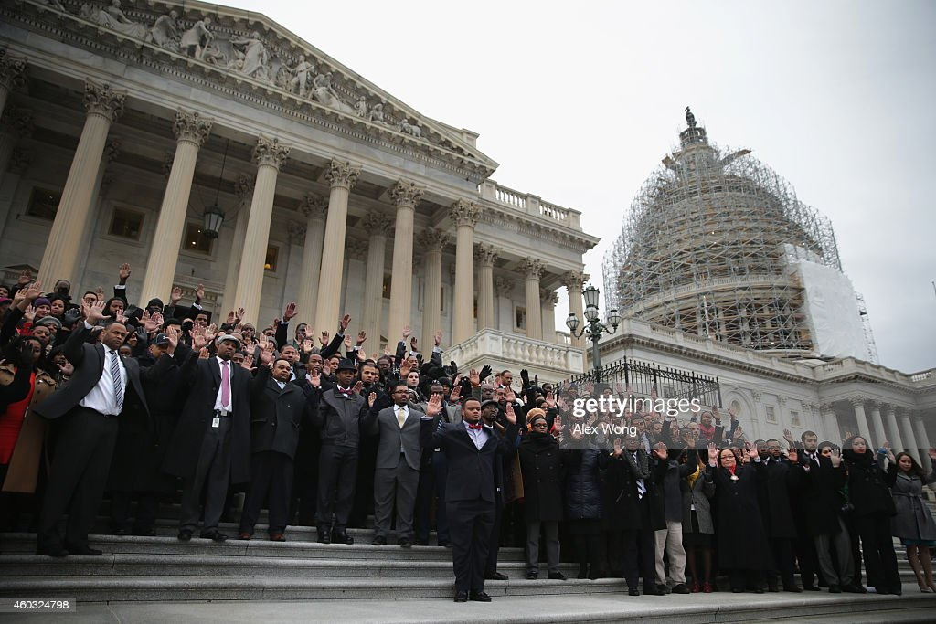 Black congressional staffers hold their hands up as they pose for a group photo during a walkout December 11 2014 on the steps of the US Capitol in...