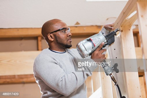 Black construction worker with nail gun