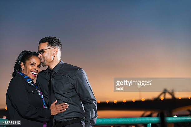 Black couple at night, sky and bridge in background