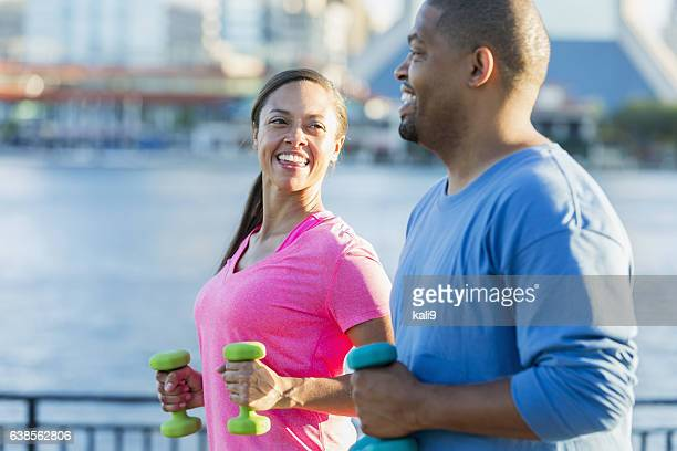 Black couple exercising together with handweights