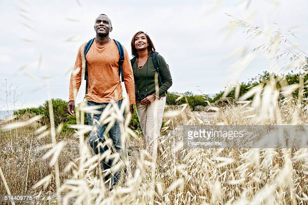 Black couple hiking on rural hillside