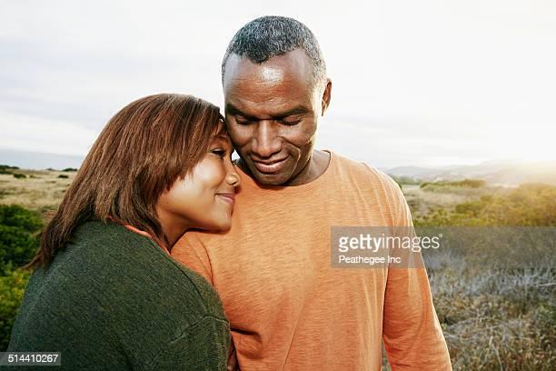 Black couple hugging on rural hillside