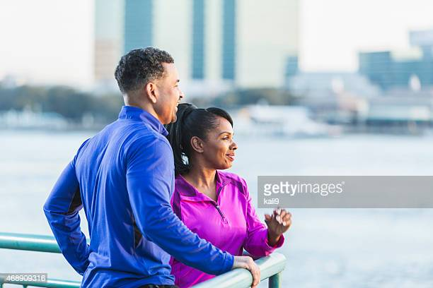 Black couple in sports clothing looking at city view
