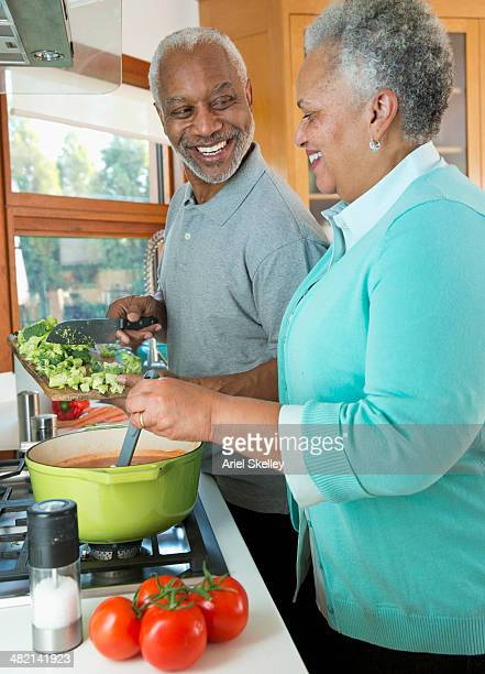 Black couple preparing vegetable soup in kitchen