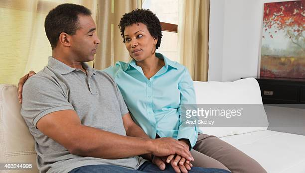Black couple relaxing on sofa